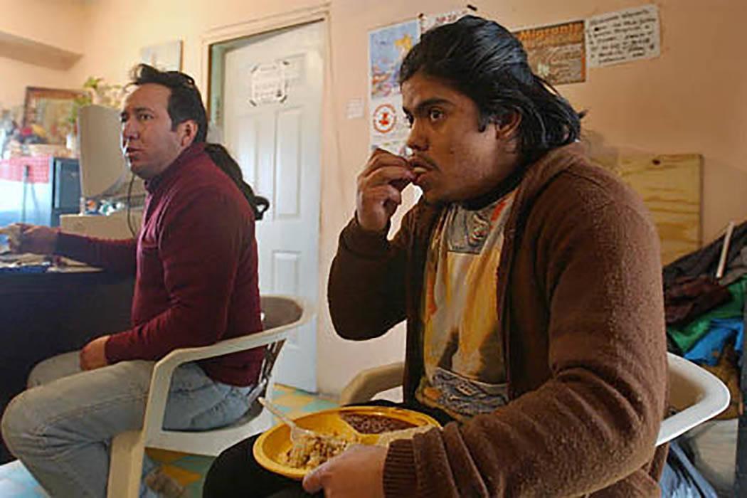 En enero 7 del 2004, los mexicanos Rodolfo Puente, de 25 años, a la derecha, y Gregorio Candelaria Cruz Ortega, de 40, comen en un albergue operado por la iglesia católica mexicana en la ciudad  ...