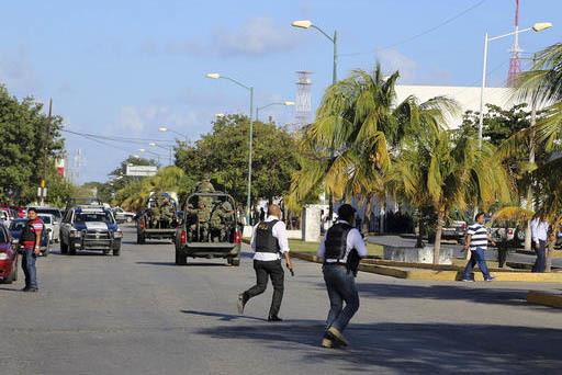 Agentes de la policía corren cerca de la oficina del fiscal del estado de Quintana Roo, luego que fue atacada por hombres armados, el martes 17 de enero del 2017 en Cancún, México. (AP Photo).