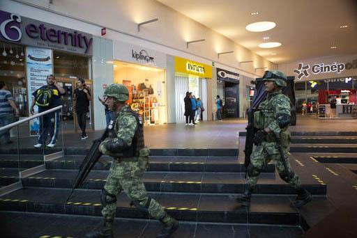 """Soldados caminan vigilantes dentro del centro comercial """"Plaza Las Americas"""" luego de reportarse disparos en Cancun, México, el martes 17 de enero del 2017. Hombres armados atacaron la oficina de ..."""