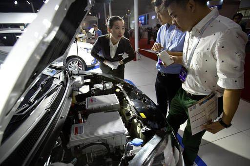 """Visitantes observan el motor de un auto eléctrico modelo iEV5 del fabricante chino """"JAC""""  durante una expo automotriz en Beijing, China, el 25 de abril del 2016. (Archivo/AP Photo/Mark Schiefelbein)."""