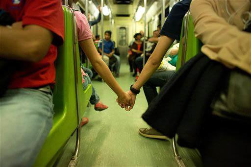 """En esta foto de archivo de Sept. 18 del 2014, se ve a una pareja sostenida de las manos que no encontró lugar para ir juntos, en las horas más ocupadas del sistema de transporte """"Metro"""", en la C ..."""