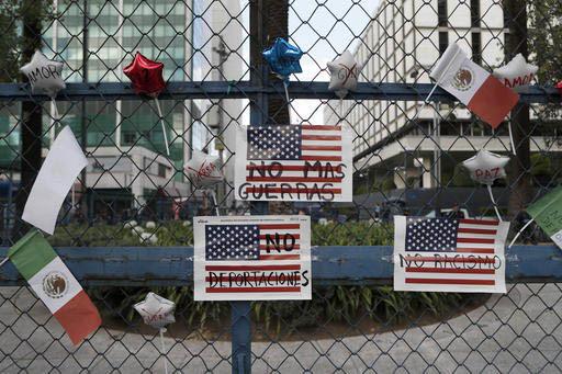 """Letreros que dicen """"no más guerras"""", """"No más deportaciones"""", """"No racismo"""", se leen en banderas de los Estados Unidos, junto a banderas de México, en una cerca que protege el frente de la embaja ..."""