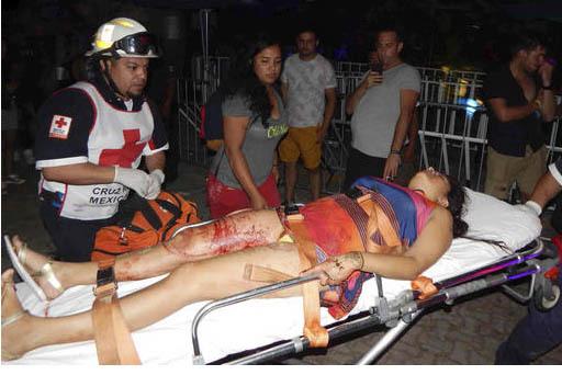 """En esta foto de """"Por Esto"""", de Quintana Roo, un socorrista presta atención a una mujer herida durante un tiroteo en el  Electronic Music festival en un club de Playa del Carmen, Mexico, en la mad ..."""