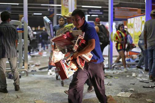 En esta gráfica se ve a un hombre corriendo con juguetes, al parecer robados de un almacén, en el puerto de Veracruz, México, el 4 de enero del 2017. Las protestas por el alza en la gasolina de ...