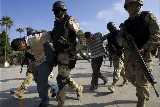 En esta foto de archivo, Dec. 3, 2008, se ve a efectivos del ejército mexicano sosteniendo a sospechosos, durante operaciones contra narcotráfico, secuestros y otros crímenes en Tijuana, Méxic ...
