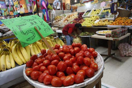 """Un puesto en el mercado """"Medellín"""" de la Ciudad de México muestra jitomate en primer plano, y otras frutas, el 2 de febrero del 2017. México exporta frutas, legumbres, electrónicos, vehículos ..."""