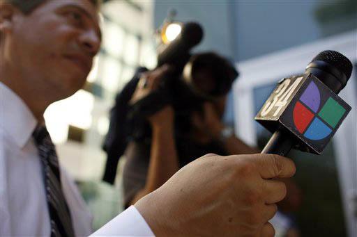 En esta foto de archivo de junio 14 del 2006 un reportero del canal KMEX 34 de Univision en Los Angeles sostiene un micrófono con el logo de la televisora. Ahora el Grupo Televisa y Univision anu ...