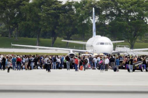 La gente se junta en la pista junto a un avión en el aeropuerto Fort Lauderdale-Hollywood, en Florida, cuando un hombre abrió fuego matando a cinco e hiriendo a otros, el viernes 6 de enero del  ...