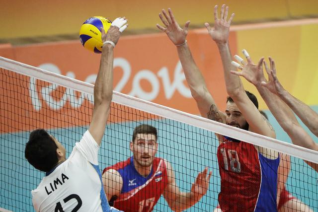 Bruno Lima de Argentina, izquierda, clava la pelota ante el ruso Alexander Volkov, derecha, intenta bloquear a Maxim Mikhaylov, centro, durante el partido de voleibol preliminar de  hombres en los ...