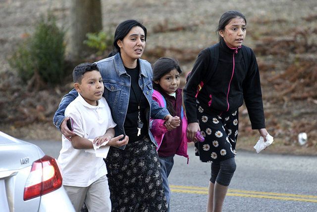 Una mujer escolta a sus tres hijos fuera del lugar del accidente donde un autobús escolar chocó y se volcó, el 21 de noviembre del 2016 en Chattanooga, Tennessee. En una conferencia de prensa l ...