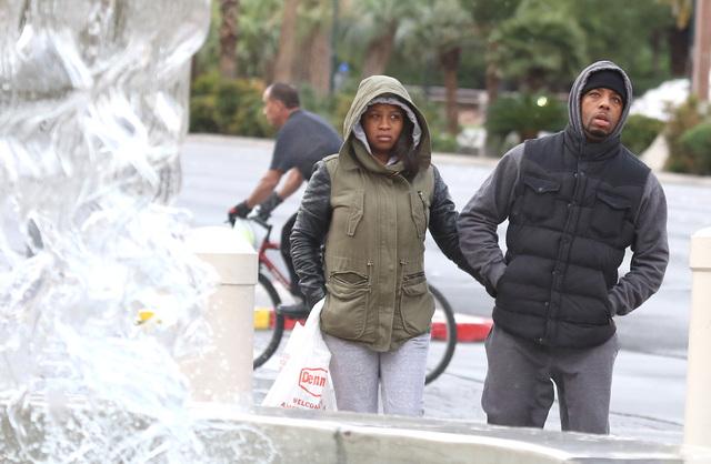 Nika Brown y Chris Jenkins, visitantes de Brooklyn, N.Y., bien abrigados caminan por el Strip, el 28 de noviembre del 2016. El Servicio Nacional del Clima pronositcó el 14 de diciembre del 2016 b ...