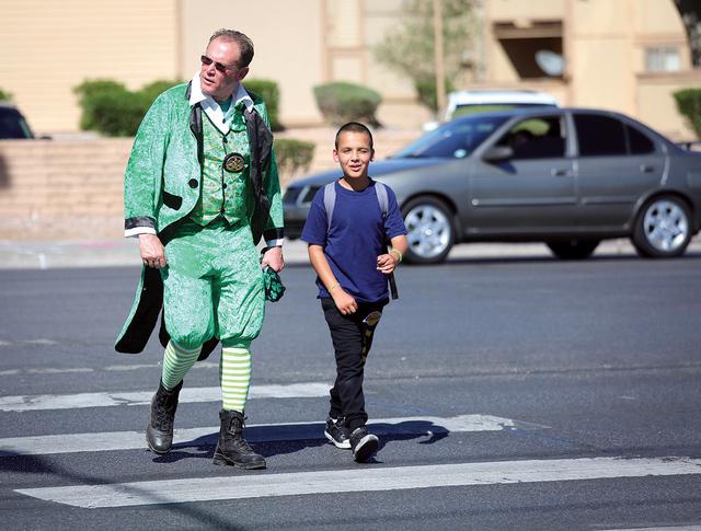 Un oficial de la policía del Distrito Escolar del Condado de Clark, ayuda a un niño a cruzar Tropicana Ave. y Morris Street, el jueves 17 de marzo de 2016. La Patrulla de Carreteras de Nevada, l ...