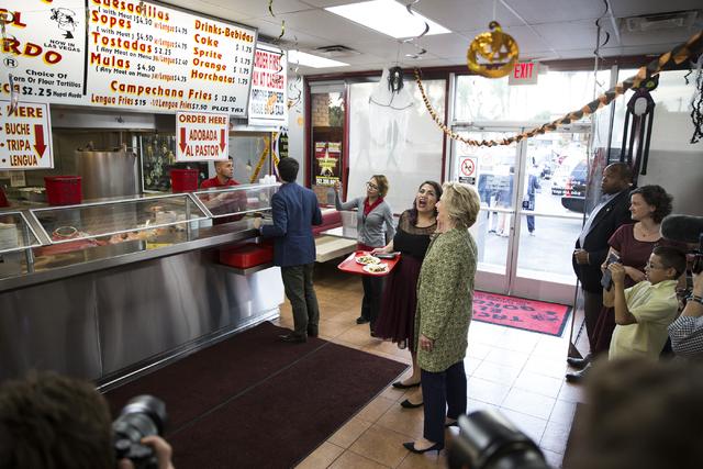 La aspirante a la presidencia Hillary Clinton, acompañada de Astrid Silva, directora de organización de Progressive Leadership Alliance of Nevada, lee el menú en Tacos El Gordo, 1724 E Charlest ...