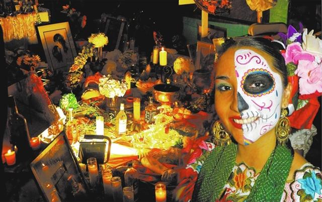 La joven Alondra Contreras, del grupo de baile folklórico Xyachimal, posa junto a una ofrenda de muertos, durante la celebración del Dia de Muertos, en noviembre del 2010, en el Centro Cultural  ...