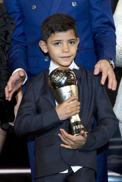 Cristiano Ronaldo Junior lleva el trofeo a su padre, Cristiano Ronaldo, de Portugal, jugando para el Real Madrid, ganó el premio al Mejor Jugador Masculino de la FIFA durante la ceremonia de los  ...