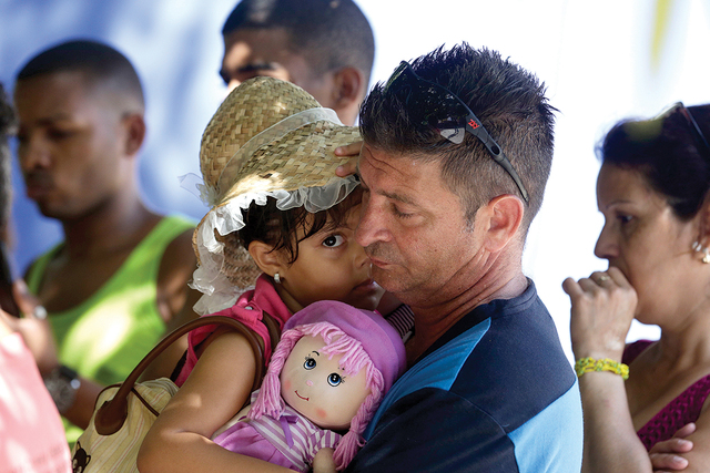 Cuban migrant Denis Gomez, 45, hold up his daughter Dalia Caridad, 4, during a meeting at a shelter in Panama City, Friday, Jan. 13, 2017. President Barack Obama announced Thursday he is ending a  ...