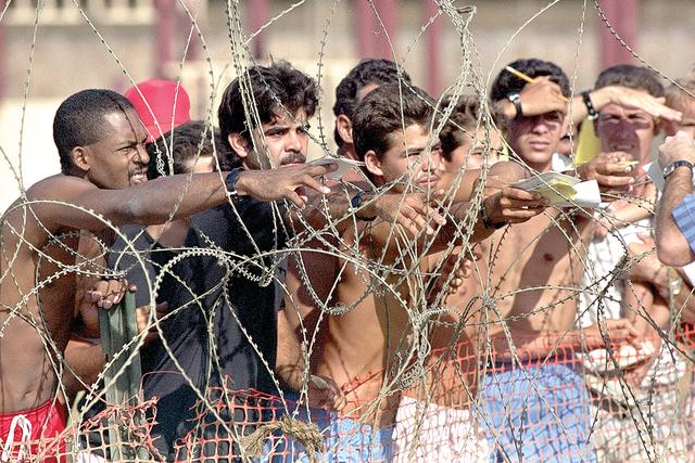 Esta foto fue tomada, el sábado 27 de agosto de 1994, muesta a refugiados cubanos que remiten notas con sus nombres al personal de la Armada para que puedan figurar en la lista de detenidos en la ...