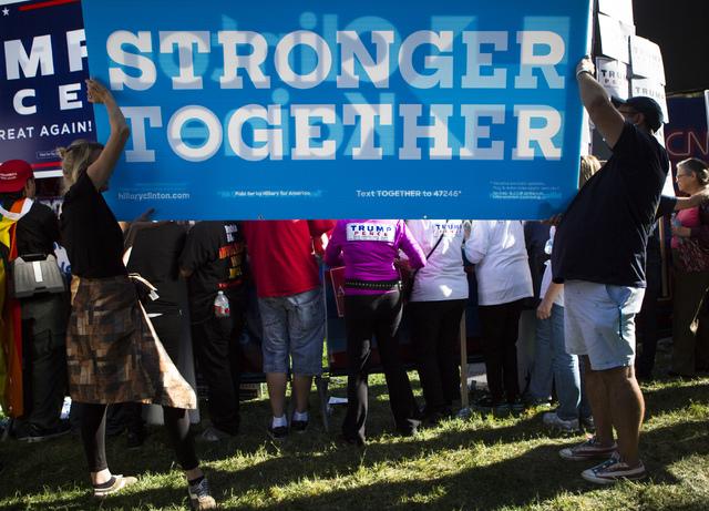 """Seguidores de la candidata demócrata Hillary Clinton sostienen una pancarta que dice """"Fuertes juntos"""", mientras detrás otro grupo en apoyo al republicano Donald Trump se expresa, frente al puest ..."""