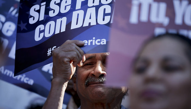 A man stands among signs during a rally in support of President Barack Obama's plan to protect more than 4 million people living illegally in the U.S. from deportation Tuesday, Feb. 17, 2015, in ...
