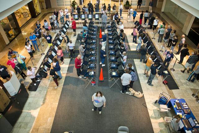 Mientras todas las máquinas de votación (al centro) están ocupadas, en las orillas se puede ver una larga fila de electores en la casilla ubicada en Galleria Sunset en Henderson, el sábado 22  ...