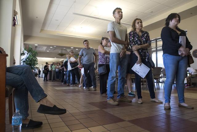 La gente espera en una larga fila su turno para votar, en la casilla electoral ubicada en el East Las Vegas Community Center durante el primer dia de la votación anticipada, el sábado 22 de octu ...