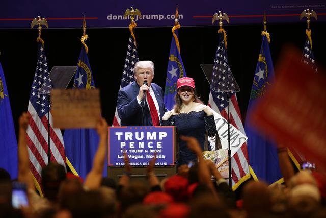"""El candidato presidencial republicano Donald Trump llamó al escenario a una mujer con un cartel que decía """"Latinas for Trump"""", durante un evento de campaña, el domingo 30 de octubre del 2016 en ..."""