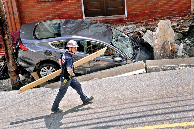 Un empleado de la construcción presta ayuda a una de las tiendas en Main Street luego que el andén se derrumbara a causa de la inundación en la ciudad de Ellicott, Maryland, el domingo 31 de ju ...