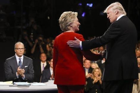 Los candidatos Hillary Clinton y Donald Trump se saludan al final de su debate presidencial en la Hofstra University en Hempstead, N.Y., mientras a la izquierda observa el periodista y moderador L ...