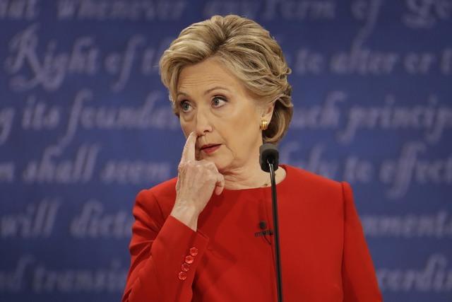 La candidata demócrata presidencial Hillary Clinton escucha a su contrincante republicano Donald Trump en el primero de sus tres debates presidenciales, en la Universidad Hofstra en Nueva York, e ...