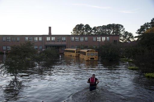 Un bombero voluntario con el Departamento de Bomberos Raynham-McDonald, camina en una área inundada frente a la  W.H. Knuckles Elementary School en Lumberton, N.C., el 10 de octubre del 2016. (AP ...