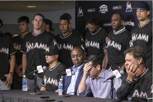 David P. Samson,  al centro de la foto, presidente de los Miami Marlins, se cubre la cara durante la conferencia de prensa para anunciar la muerte del pitcher José Fernández, de 24 años de edad ...