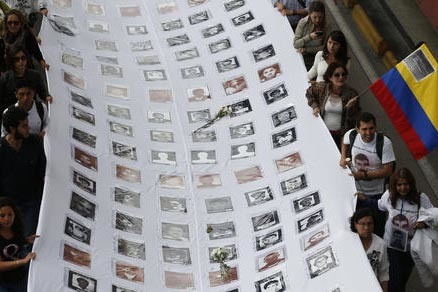 Manifestantes muestran con una enorme manta a las víctimas de la violencia en Colombia durante una marcha para demandar la paz, en Bogotá, el 12 de octubre del 2016. (AP Photo/Fernando Vergara).