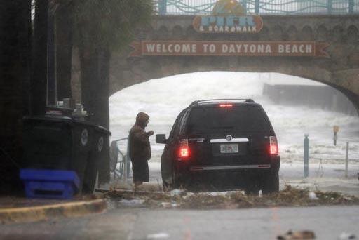 Brian Johns habla con un oficial mientras mira los efectos del huracán Matthew, el viernes 7 de octubre del 2016, en Daytona Beach, Florida. (Foto AP/Eric Gay).