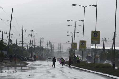 Gente cruza la calle en el centro de Kingston, Jamaica, el domingo2 de  Octubre del 2016, en medio de lluvias provocadas por el huracán Matthew. (AP Photo/Collin Reid).
