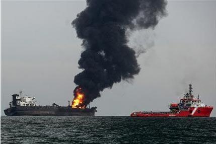 Un barco de asistencia pasa junto al petrolero incendiado Burgos, un día después de que comenzara el fuego en la costa de la ciudad portuaria de Boca del Río, en México, el dom ...