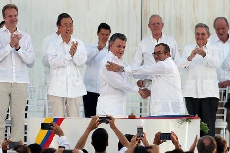 El presidente de Colombia, Juan Manuel Santos, al frente a la izquierda, y el comandante de las FARC Rodrigo Londoño,  se saludan para sellar la firma del acuerdo de paz. Observan dignatarios de  ...
