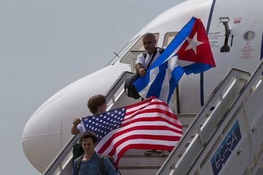 Dos pasajeros del vuelo 387 de JetBlue, agitan las banderas cubana y estadounidense al llegar al aeropuerto de Santa Clara, Cuba, procedente de los Estados Unidos. Fue el primer vuelo comercial de ...