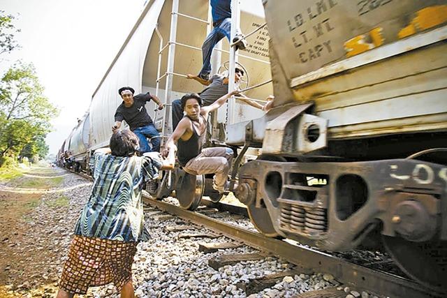 """Una mujer de las que se conocen como """"Las Patronas"""" distribuye comida a los migrantes que pasan por tren en algún lugar de México. (Foto Cortesía)."""