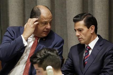 El presidente de México Enrique Peña Nieto (der) conversa con su colega costarricense Luis Guillermo Solís durante la Cumbre de Refugiados y Migrantes de la ONU el 19 de septiembre del 2016. (A ...