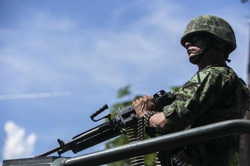El domingo 2 de octubre del 2016 un soldado del ejército mexicano se mantiene vigilante en un vehículo militar que lleva los cuerpos de soldados muertos el día anterior en una emboscada, en la  ...