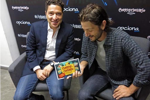 """El actor mexicano Diego Luna, a la derecha, y el activista Alejandro Legorreta, de la organización """"NGO Opciona"""" muestran una copia del libro titulado """"Corrupcionario"""", el 27 de septiembre de ..."""