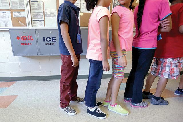 Niños inmigrantes detenidos se alinean en la cafetería en el Centro Residencial del Condado de Karnes, un hogar temporal para las mujeres y niños inmigrantes detenidos en la frontera, Karnes Ci ...