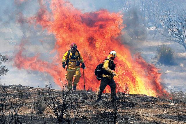 Bomberos se alejan de la llamarada mientras trabajan en apagar el fuego cerca del pueblo de Acton, Calif., el lunes 25 de julio, 2016. (AP Photo/Nick Ut)
