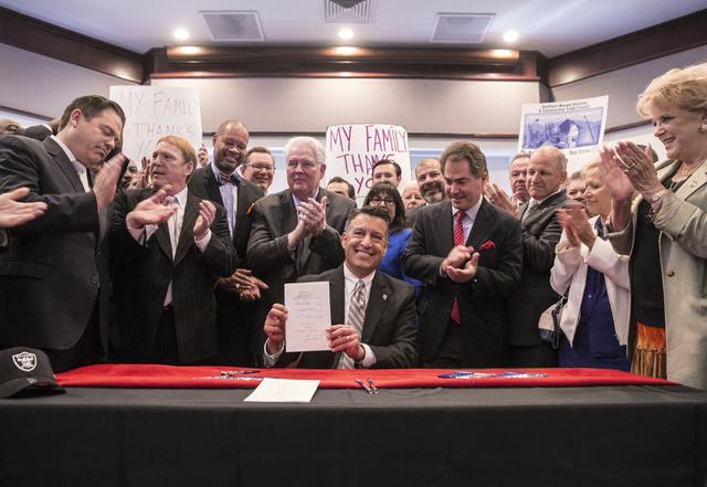 """El gobernador de Nevada, Brian Sandoval, celebra después de firmar la propuesta de Ley SB-1 del senado estatal, en el """"Richard TAM Alumni Center"""" de la UNLV, el lunes 17 de octubre del 2016, en L ..."""