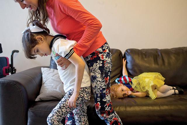 Mayela Benavides ayuda a su hija Graciela a caminar dentro de su casa en Monterrey, México, el jueves 29 de octubre de 2015. El niño de 8 años de edad tiene el síndrome de Lennox- Gastaut, una ...