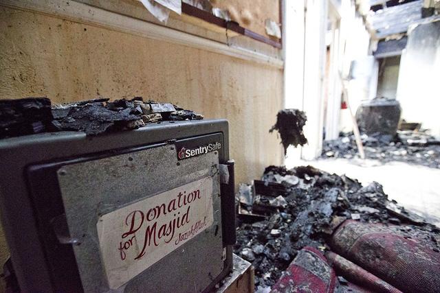 Una caja fuertte para donaciones para el Centro Islámico de Fort Pierce se muestra en el interior restos carbonizados del centro, jueves, 15 de de septiembre, 2016, en Fort Pierce, Florida. Un ex ...