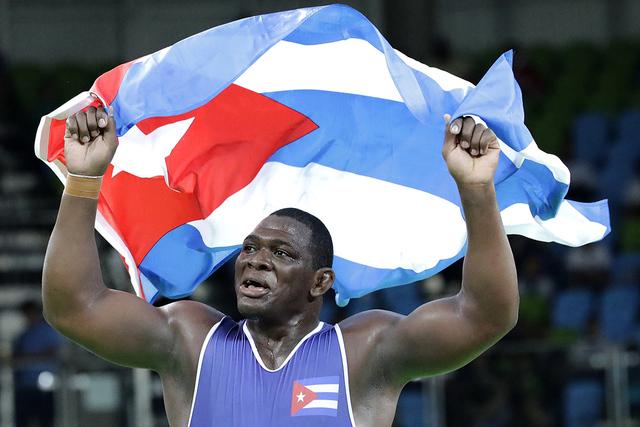 El luchador cubano Mijain Lopez Nunez celebra luego de ganar medalla de oro al vencer al turco Riza Kayaalp. La competencia fue en lucha Greco-Roman 130-kg.  / AP Photo/Charlie Riedel.