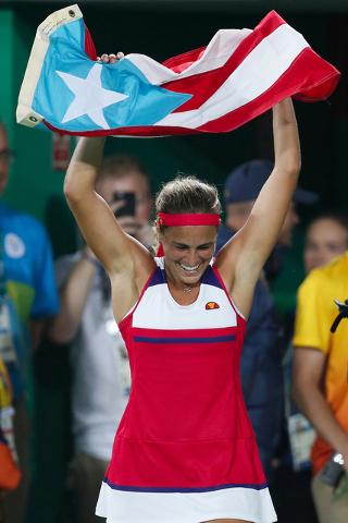 Mónica Puig de Puerto Rico celebra sosteniendo la bandera de su país después de ganar la medalla de oro en la competencia de tenis de las mujeres en los Juegos Olímpicos 2016 en Río de Janeir ...