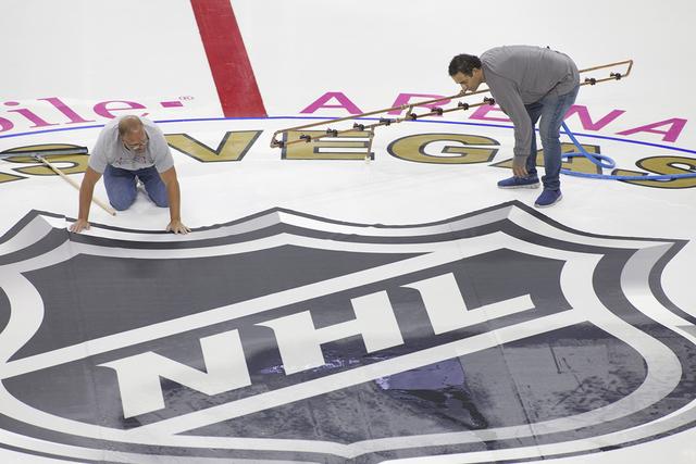 Personal instala el logo de la NHL en la pista 2016 en T-Mobile Arena en Las Vegas. Loren de hielo el sábado 30 de julio de Townsley/Las Vegas Review-Journal