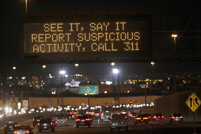 """Un aviso luminoso dice: """"Ve algo. Diga algo. Reporte la actividad sospechosa, llame al 311"""". Hay varios avisos como este en el valle; éste está en la carretera 95 hacia el norte cerca de Rancho, ..."""